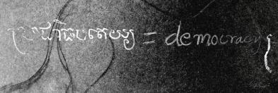 "Khmer script next to the english translation: ""democracy."""