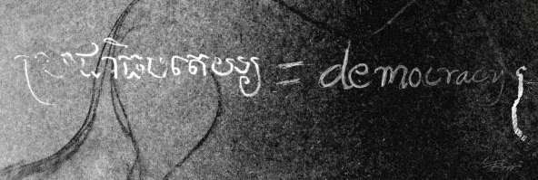 "Khmer script next to the english translation: ""democracy."""