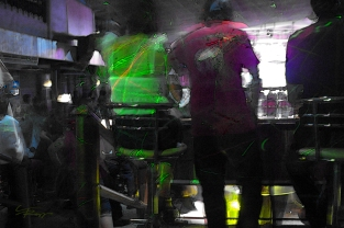 Light plays off the backs of people getting a drink at a club in Thailand.