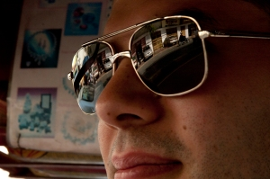 A Cambodian motorist is reflected in the sunglasses of a tourist.