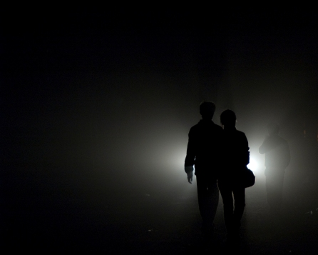 Two figures can be seen silhouetted against a light in Hefei, Anhui Province, China.