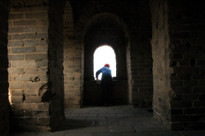 A Chinese tourist peers out of a tower in the Great Wall of China.