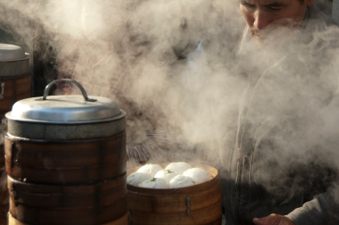 Steam rolls out of baskets as a street vendor prepares boazi, a local delicacy.