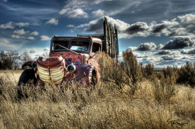 An old truck sits abandoned in a farmers field.