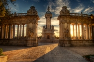 Sun setting over Alfonso XII monument, Parque del Retiro, Madrid, Spain.